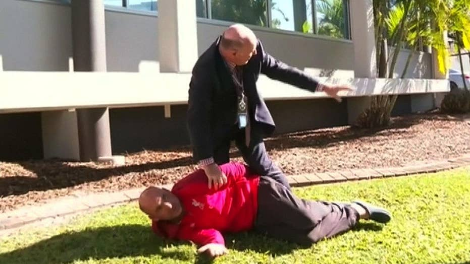 Australian police detective stops news conference to tackle man