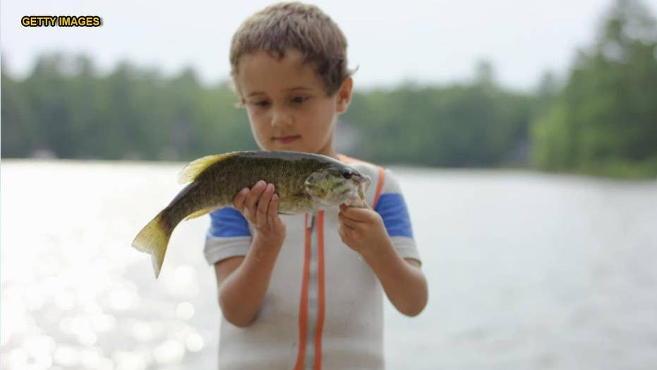 Mom doesn't realize kid shoved a fish in his mouth in family photo