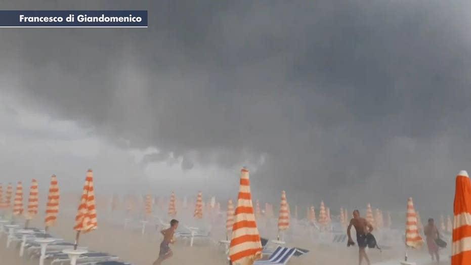 Sunbathers flee as freak storm hits beach in Italy