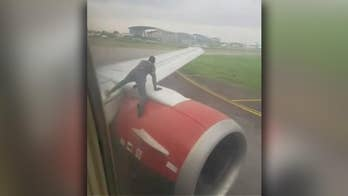 Raw video: Intruder climbs onto the engine of a plane just before takeoff from Nigeria's busiest airport
