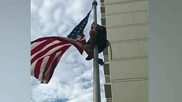 Retired Navy SEAL climbs flag pole to fix flag