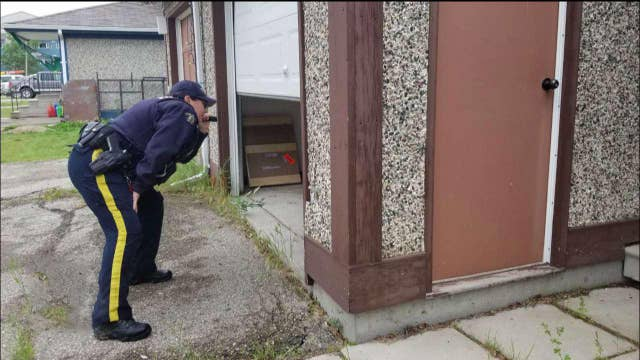 Canadian police conduct door-to-door search for suspects in murder of an American and two others