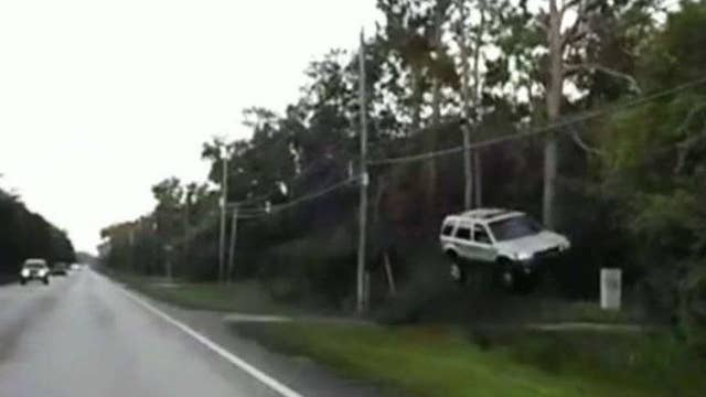 SUV flies off road, officer rushes in to help