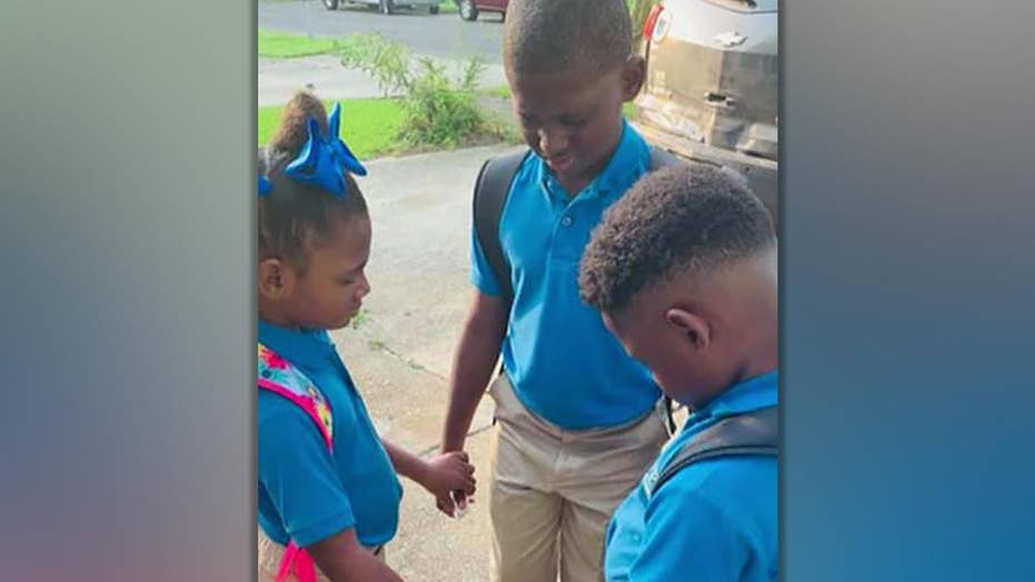 Photo of siblings praying on first day of school goes viral as family faces tough times