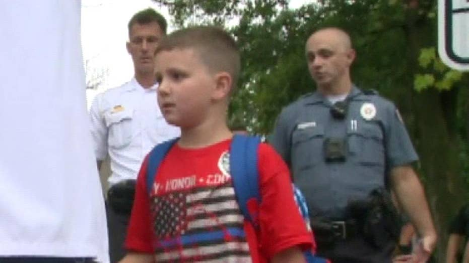 Police officers walk fellow officer's autistic son to his first day of school