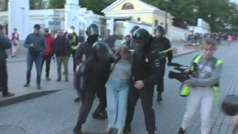 Russian policeman punches female protester during Moscow protest