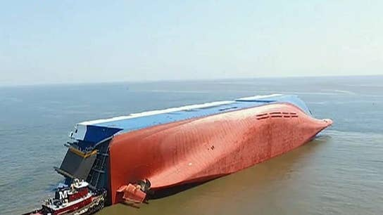 Coast Guard says 4 trapped crew members are alive on overturned cargo ship