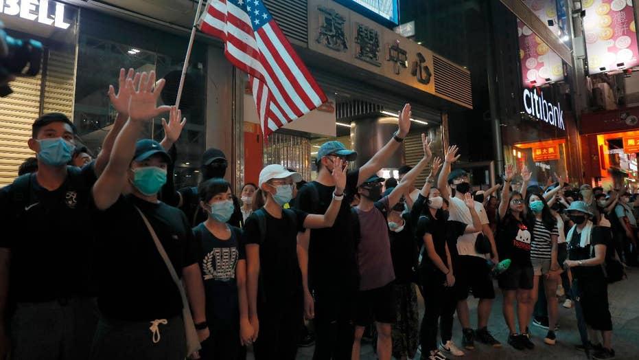 Hong Kong demonstrators wear face masks in defiance of ban