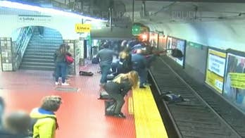 Argentina commuters rescue woman pushed onto tracks in front of oncoming train in harrowing video