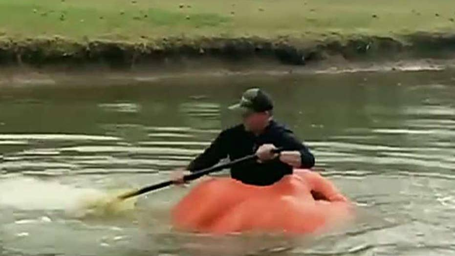 Man uses giant pumpkin as a boat