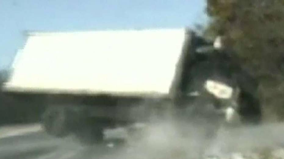 Runaway truck narrowly misses state troopers helping woman change tire on side of road
