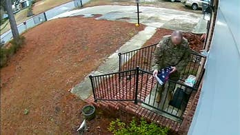 Man in military garb folds flag torn from pole during a storm, returns it to owners porch