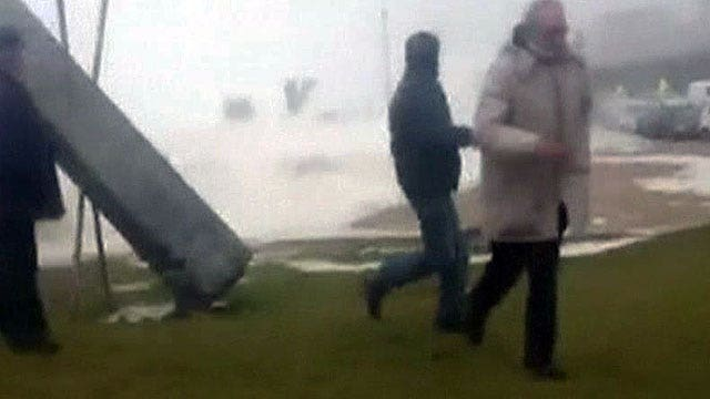 Wipe out: Spectators scatter when massive wave jumps seawall