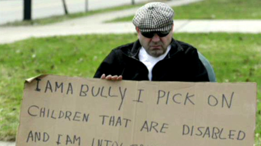 Man forced to sit on corner with 'I AM A BULLY' sign