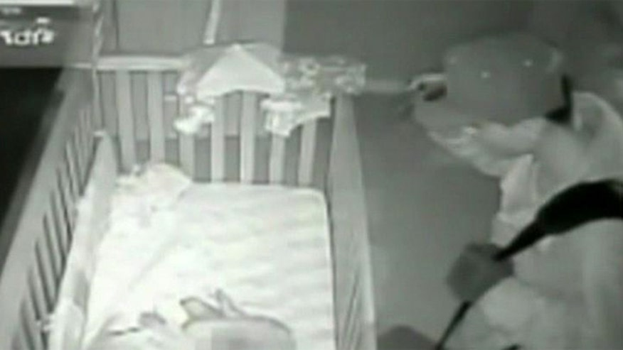 Surveillance camera reveals intruder standing over sleeping infant