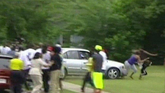 Wild scene as murder suspect's dad crashes car through crowd