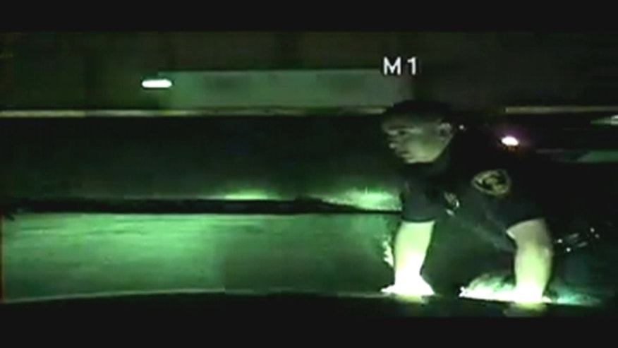 A Houston-area police officer has been praised as a hero for dragging a woman off some railroad tracks just moments before a train rushes by.