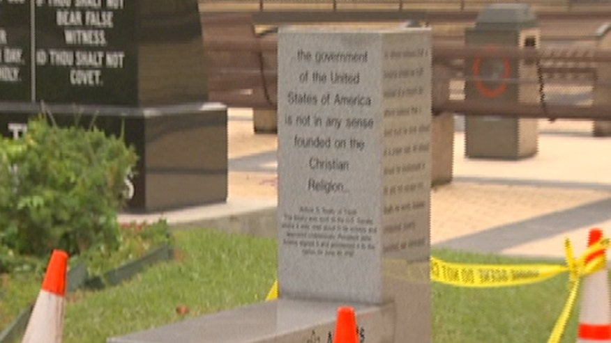 Monument stands next to statue of Ten Commandments