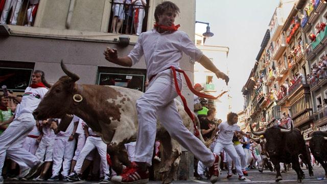 Bulls, thrill-seekers dash through streets of Pamplona