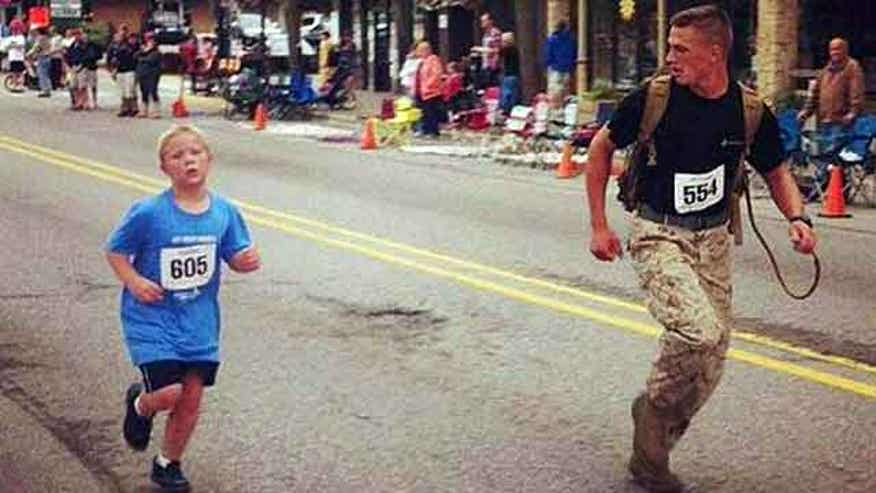 Lance Corporal Myles Kerr encourages little boy in Michigan