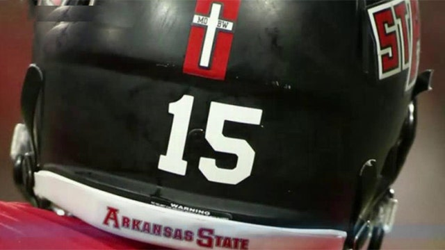 College football team forced to removed cross from helmets