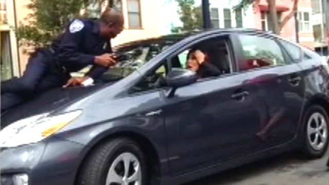 Reckless driver flees with parking officer on hood of car