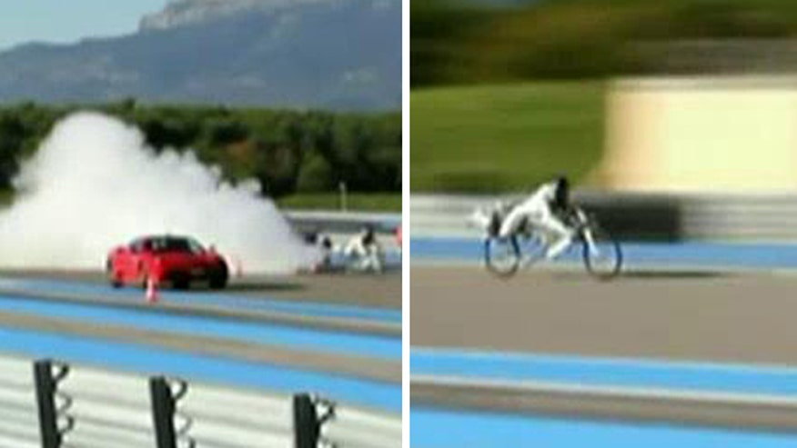 Man reaches 207 mph rocket-powered bike while racing sports car