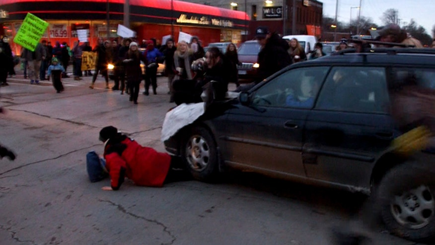 Driver who hit protesters not charged, incident under review