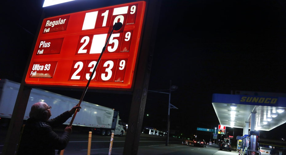 Gas station owner changing price sign FBN