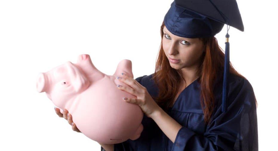 Graduate Holding Empty Piggy Bank