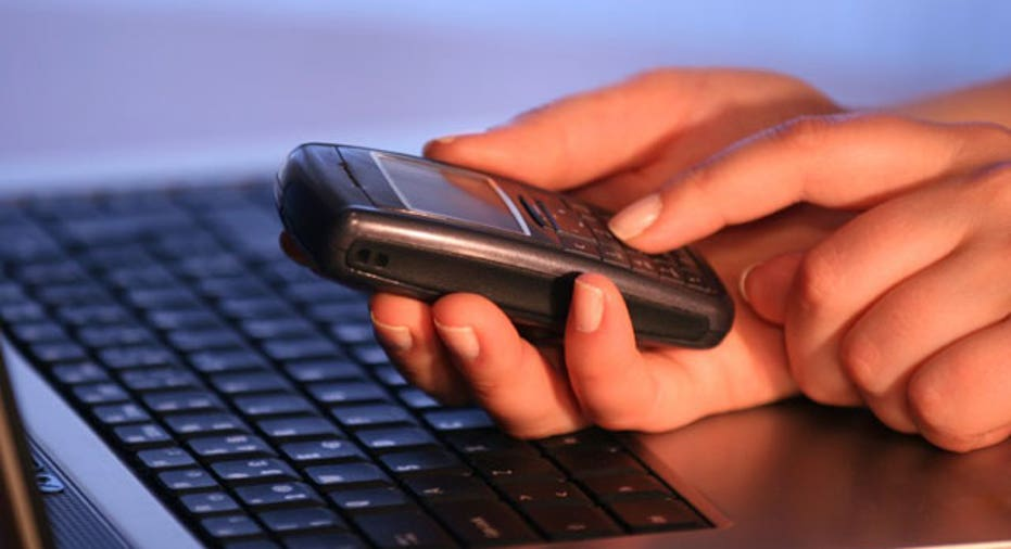 Man Using Cell Phone and Laptop