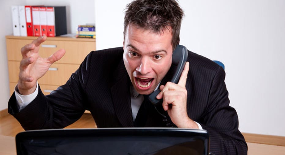 Man Angry at Computer on Phone in Office