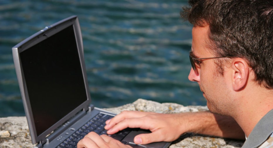 Man Using Laptop Near Beach