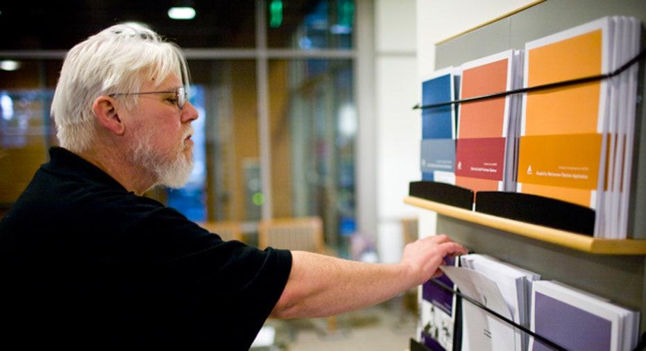Elderly Man Looks Through Retirement Pamphlets
