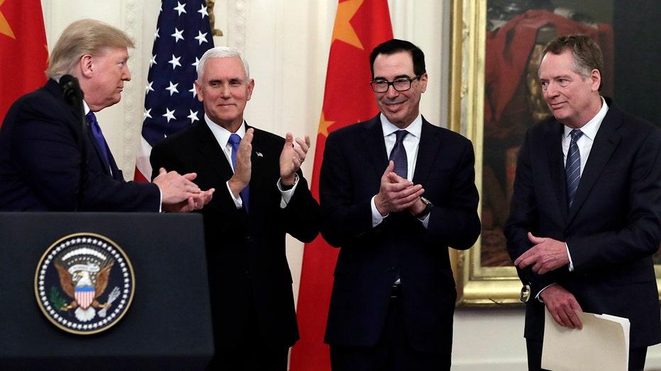 Trump acknowledges Vice President Mike Pence, Treasury Secretary Steven Mnuchin and U.S. Trade Representative Robert Lighthizer. (AP Photo/Evan Vucci)