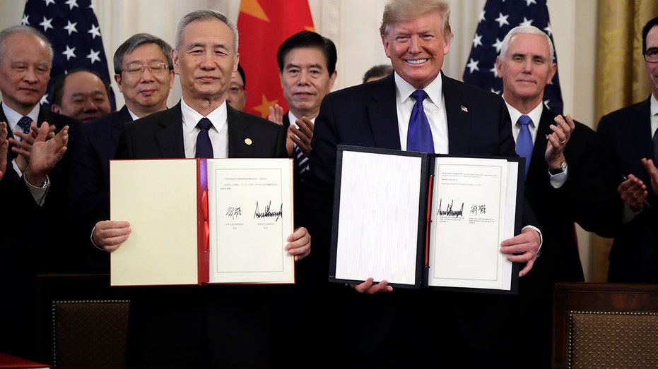 President Trump signs a trade agreement with Chinese Vice Premier Liu He, in the East Room of the White House, Wednesday. (AP Photo/Evan Vucci)
