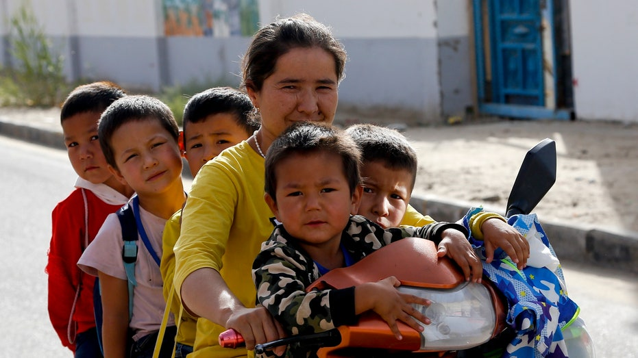 Uighur woman and children at the Unity New Village in Hotan, in western China's Xinjiang region.