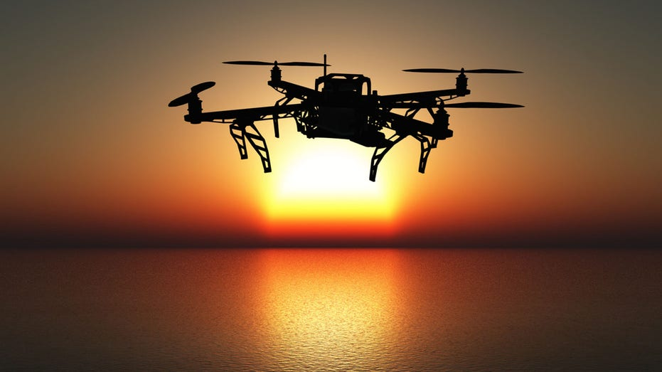 3D drone flying above a sunset sea