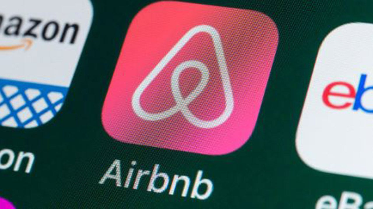 Airbnb cuts loss, shares fall as COVID clouds forecast