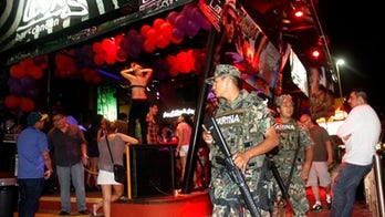 Youths flood Cancun under watch of marines, police