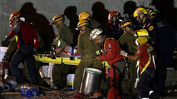 A female firefighter is carried out on a stretcher after spraining her ankle as rescue workers race against the clock to reach possible survivors trapped inside an office building in the Roma Norte neighborhood of Mexico City,