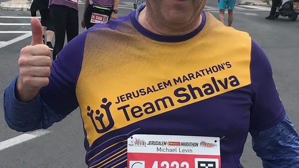 A photo of the author running in Jerusalem with the Old City in the background.