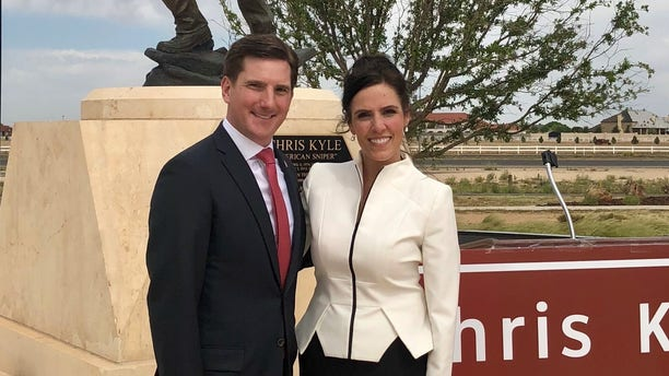 Texas State Rep. Brooks Landgraf and Taya Kyle standing before the Chris Kyle Memorial Highway in Odessa, Texas, on May 8, 2018.