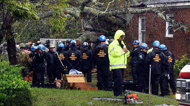 Rescue workers, police and fire department members wait to remove the bodies of a mother and child who were killed by a falling tree as Hurricane Florence made landfall in Wilmington, N.C. Friday Sept. 14, 2018. The father was transported to the hospital with serious injuries. (Chuck Liddy/The News & Observer via AP)