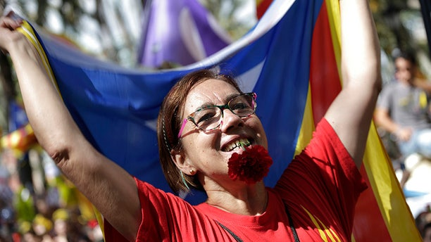 A woman holds a flower in her teeth and waves the ''estelada'' or Catalonia independence flags during a protest in Barcelona, Spain Thursday, Sept. 21, 2017.