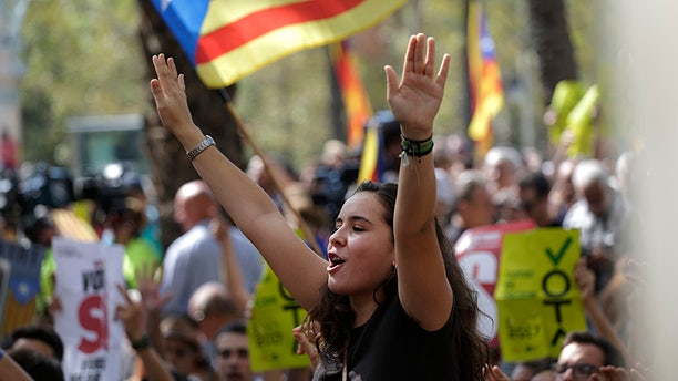 A woman gestures as others wave the ''estelada'' or Catalonia independence flags during a protest in Barcelona, Spain Thursday, Sept. 21, 2017.