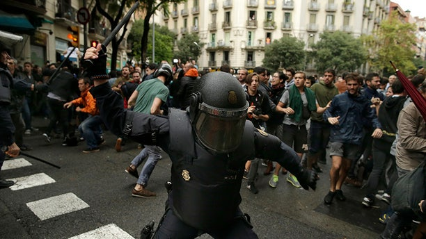 FILE, In this Sunday, Oct. 1, 2017 photo, a Spanish riot police swings a club against would-be voters near a school assigned to be a polling station by the Catalan government in Barcelona, Spain, Sunday, Oct. 1, 2017. (AP Photo/Manu Fernandez, File)