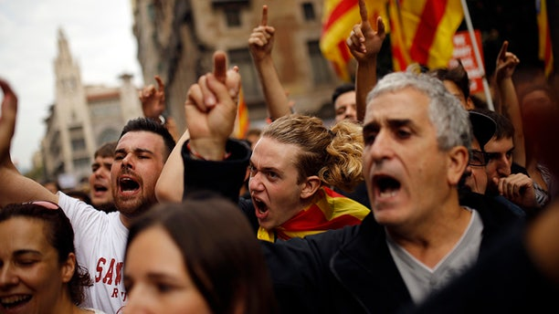 Protesters shout as they gather in front of the Spanish police station in downtown Barcelona, Spain, Tuesday Oct. 3, 2017.