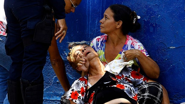 A woman is overcome by tear gas that was used to disperse the relatives of prisoners who were waiting to hear news about their family members imprisoned at a police station where a riot broke out, in Valencia, Venezuela.