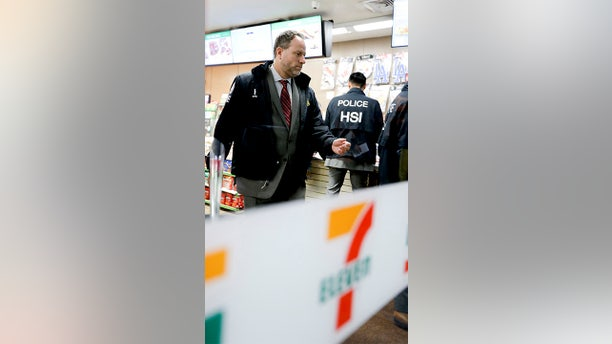 Christopher Kuemmerle, a group supervisor for U.S. immigration and Customs Enforcement's Homeland Security Investigations unit watches as agents serve an employment audit notice at a 7-Eleven convenience store Wednesday, Jan. 10, 2018, in Los Angeles, Calif.